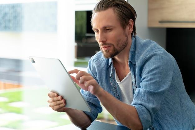 Close-up op man die thuis een digitaal apparaat gebruikt