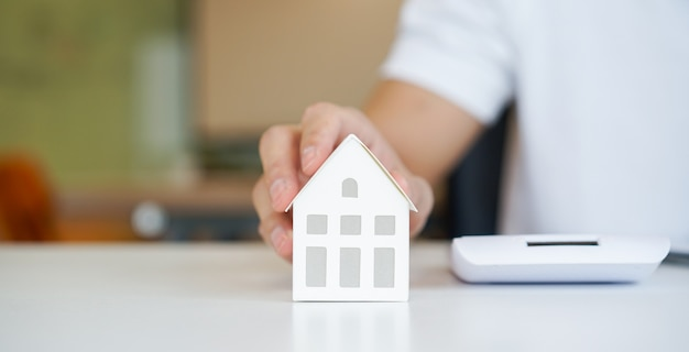 Close-up op man hand aanraken home-model op de tafel voor lening hypotheek en herfinancieren plan