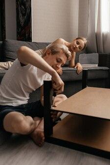 Close-up op man repaing een tafel in zijn woonkamer met een schroevendraaier
