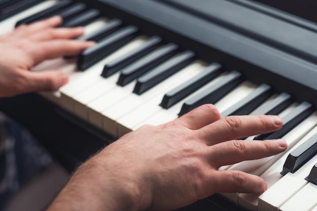 Close-up op man spelen op piano