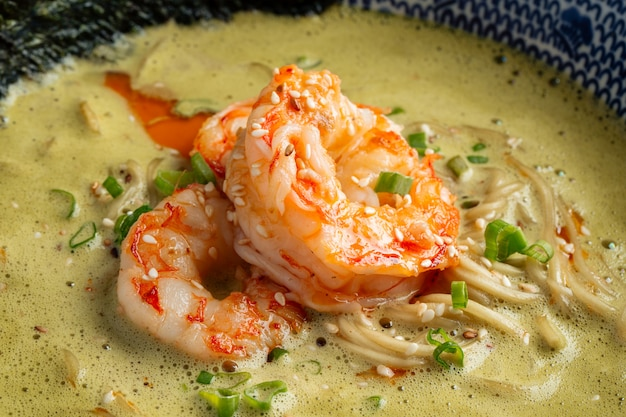 Close-up op matcha ramen soep met langoustines