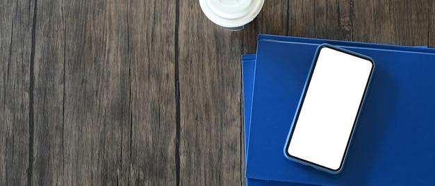 Close-up op mobiele telefoon met wit scherm, notebook op houten tafel