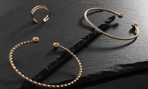 Close-up op moderne armband met diamanten en moderne ring op zwarte stenen platen
