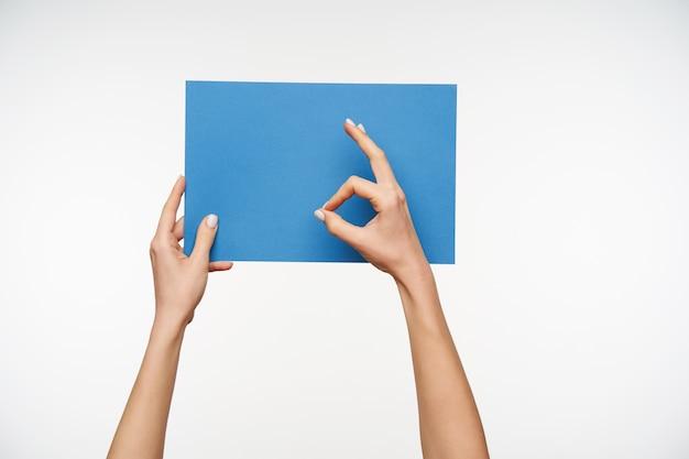 Close-up op mooie handen met blanco vel papier