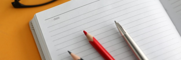 Close-up, op open dagboek liggen kleurpotloden en pen