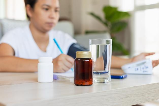 Close-up op pillenfles en een glas water terwijl aziatische jonge vrouw thuis bloeddruk en hartslag controleert met digitale manometer. gezondheid en medisch concept.