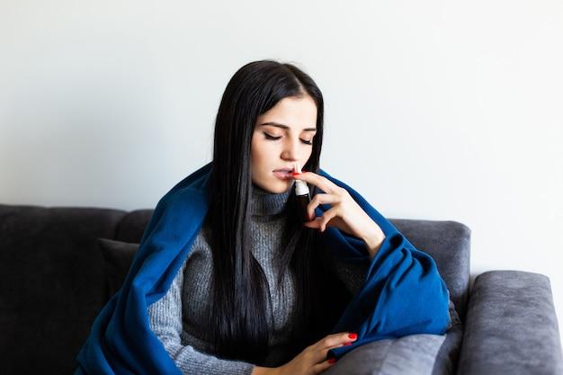 Close-up op pillenpak ter beschikking van zieke jonge vrouw die op bank legt