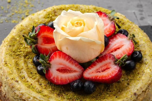 Close-up op pistache cheesecake gegarneerd met bessen en roos