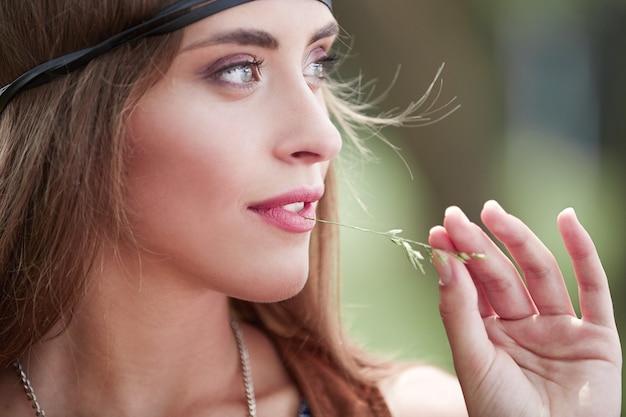 Close-up op portret van een vrouwelijke hippie op onscherpe achtergrond van bos