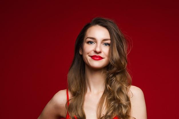 Close-up op prachtige jonge volwassen vrouw met lang golvend bruin haar glimlachend in de camera met dikke rode lippen. geïsoleerd op rood.