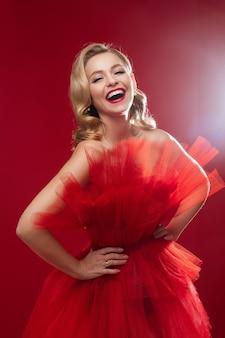 Close-up op prachtige positieve blonde vrouw met mooie rode jurk met tutu