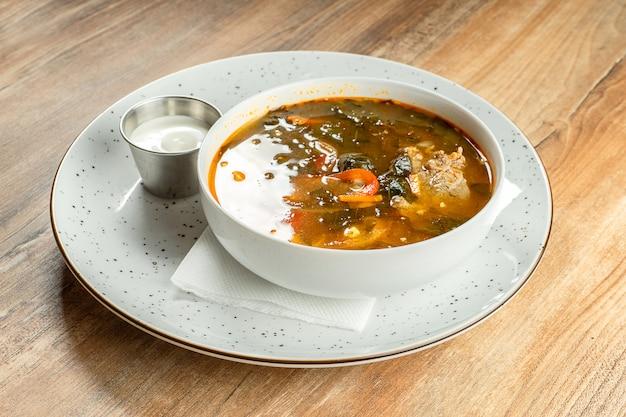 Close-up op restaurant geserveerd groene borsjt met zure room, zuring en vlees. oekraïense keuken. lekkere soep in witte kom.