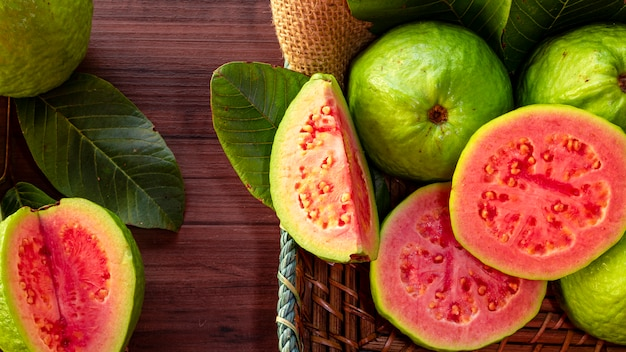 Close-up op rode guave die met groen blad op rustieke houten lijst wordt gesneden