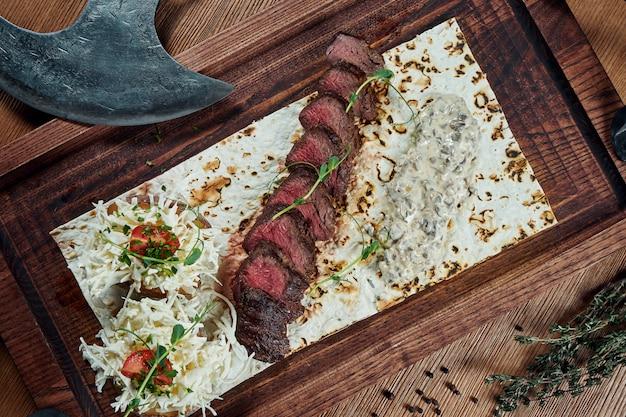 Close-up op rundvlees filet of gesneden biefstuk medium rood met een bijgerecht van gebakken aardappelen en champignonsalade op een houten bord. biersnack, lekker eten