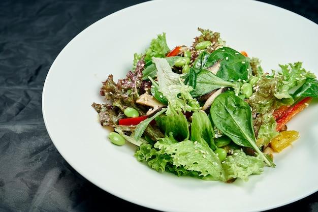 Close-up op salade met spinazie, champignons, paprika, jonge bonen en erwten in een witte kom op een zwarte tafel. gezond en dieetvoeding. vegetarisch