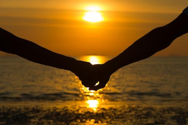 Close-up op silhouet van paar armen hand in hand bij zonsondergang aan zee. romantische huwelijksreis, liefdeconcept