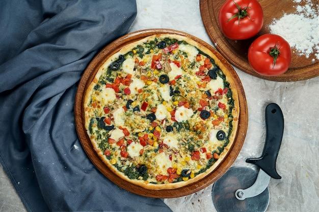 Close-up op smakelijk pizza met vegetarische vulling: pesto, tomaten, maïs, paprika, ui op houten tafel in een restaurant. italiaanse keuken.