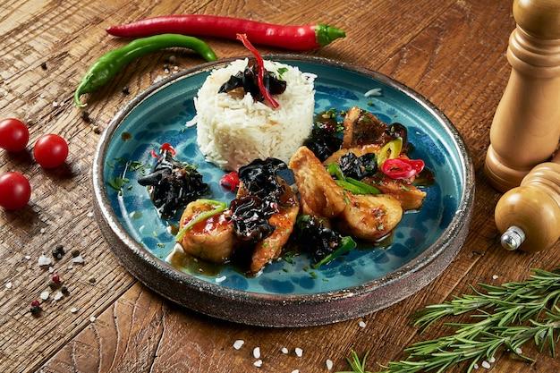 Close-up op smakelijke en sappige vis snoekbaars zoetzure saus en chili met jasmijnrijst op een blauwe keramische plaat in een compositie met kruiden op een houten oppervlak