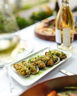 Close-up op smakelijke mosselen met vulling op de witte geserveerd tafel