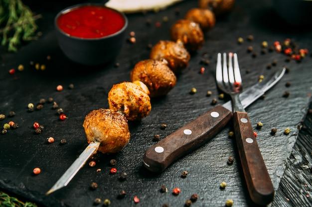 Close-up op smakelijke paddestoel kebab shashlyk spiesjes met rode saus en gepekelde ui op een zwarte bord op een donkere houten achtergrond