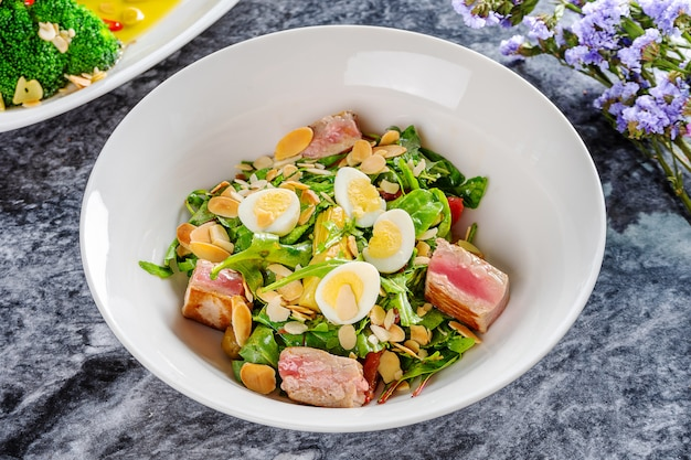 Close-up op smakelijke salade met gegrilde tonijn, microgroen, klein ei op marmeren tafel. mediterrane en italiaanse keuken. italiaans voorgerecht. plat liggen. zeevruchten. helathy maaltijd
