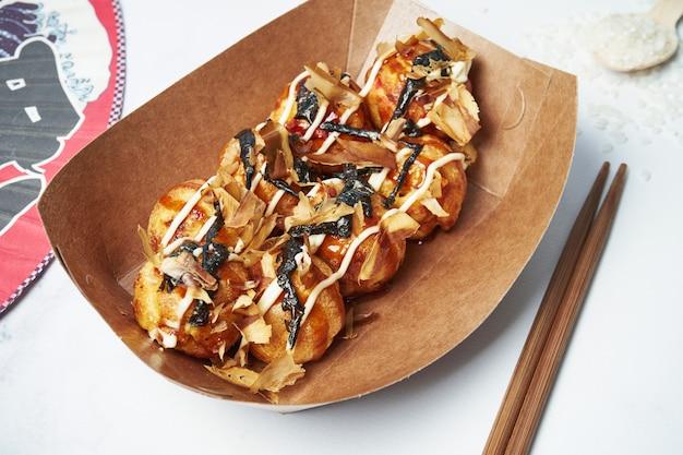 Close-up op smakelijke takoyaki - japanse snack of aperitief gemaakt van een op tarwebloem gebaseerd beslag gevuld met gehakte of in blokjes gesneden octopus. straatvoedsel. selectieve aandacht