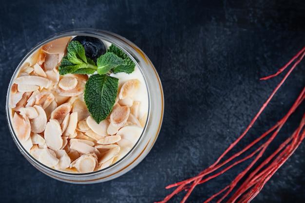 Close-up op smakelijke tiramisu met noten en mango. dessert geserveerd op donkere achtergrond met kopie ruimte. afbeelding voor menu of recept.