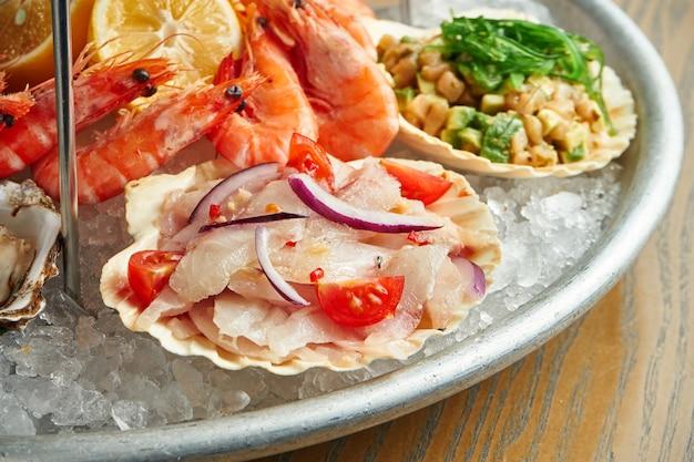 Close-up op tartaar van zeebaars met tomaat en ui in een shell in een plaat op ijs