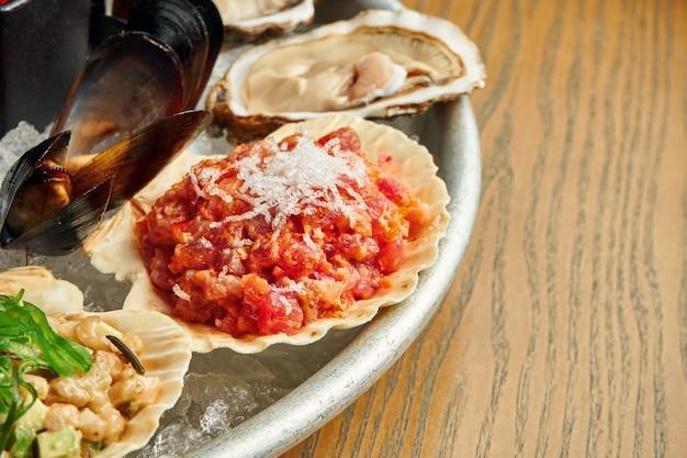 Close-up op. tonijntartaar met tomaat en ui in shell in een plaat op ijs