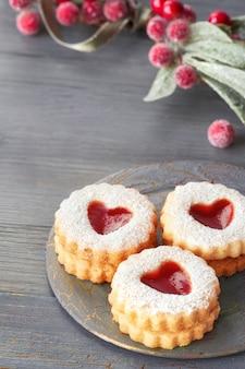 Close-up op traditionele kerstmis linzer-koekjes die met aardbeijam worden gevuld op grijs met kerstmisdecoratie