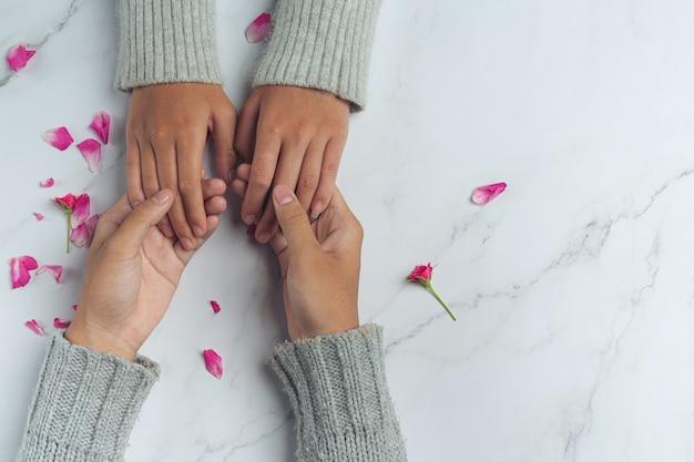 Close-up op twee jonge geliefden hand in hand aan een tafel.