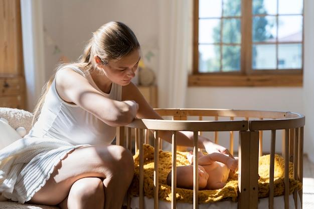 Close-up op vermoeide moeder die voor pasgeboren baby zorgt