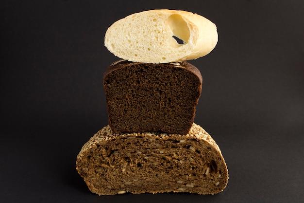 Close-up op verschillende soorten brood op de zwarte achtergrond