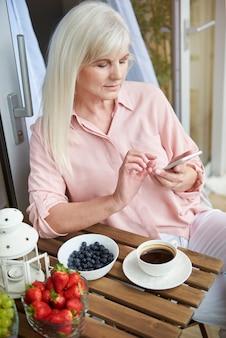 Close-up op volwassen vrouw genieten van goede koffie op het balkon