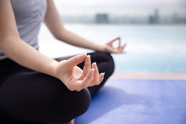 Close-up op vrouw beoefenen van yoga met sukhasna vormen bij het zwembad