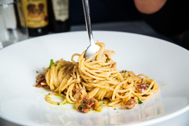 Close-up op vrouw die italiaanse spaghetticarbonara met witte wijn eet