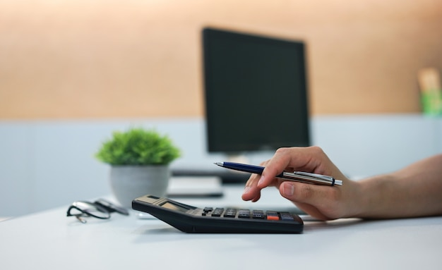 Close-up op werknemer man vinger druk op rekenmachine voor het beheren van kosten concept