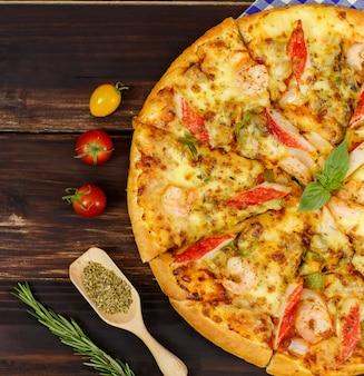 Close-up op zelfgemaakte zeevruchten pizza met garnalen, krabsticks, paprika topping op houten plaat, versierd met tomaten, oregano ingrediënten in de keuken.