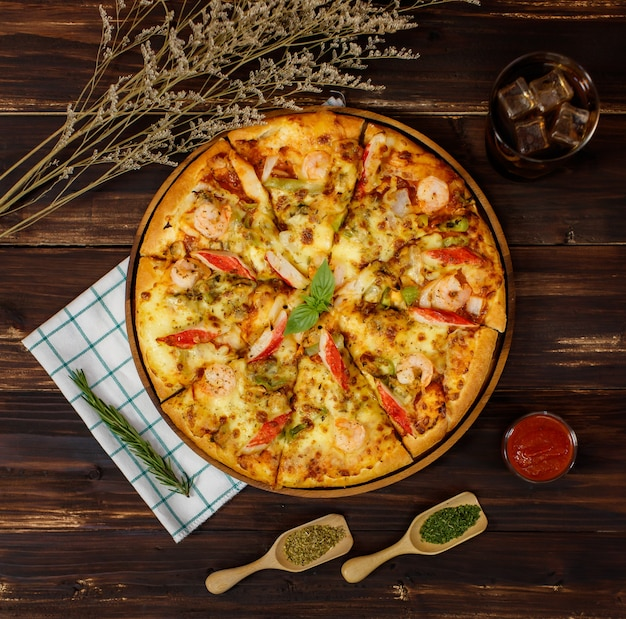 Close-up op zelfgemaakte zeevruchten pizza met garnalen, paprika, krabsticks op houten tafel met koude drank, servet, ingrediënt van tomatensaus of ketchup, gedroogde planten, paprikapoeder, oregano.