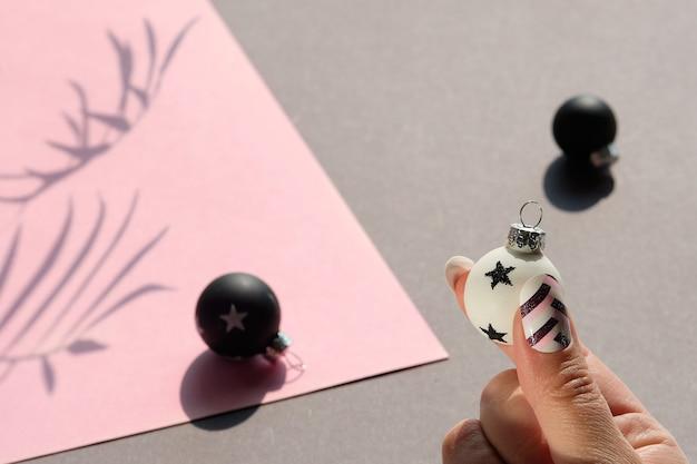 Close-up op zwart-witte kerstballen op roze en grijs gelaagd papier.