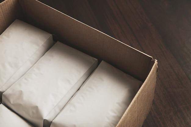 Close-up opende grote kartonnen doos vol met lege hermetische witte pakketten met koffie of thee