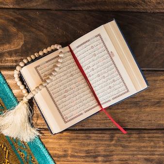 Close-up opende koran en kralen in de buurt van mat