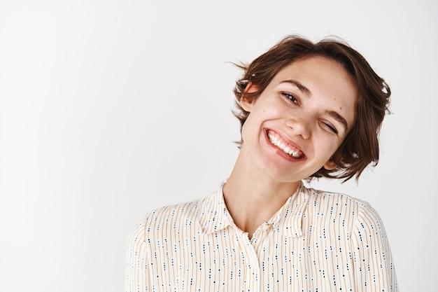 Close-up openhartig portret van een mooie vrouw die haar hoofd kantelt en glimlacht, blije uiting van vreugde en positiviteit, staande op een witte muur