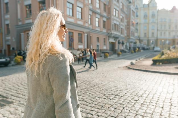 Close-up openluchtportret van jonge glimlachende blonde vrouw
