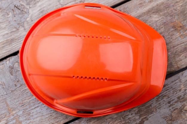 Close-up oranje constructor's helm. oude leeftijd tafel op de achtergrond.
