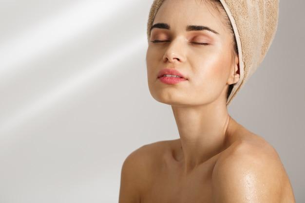 Close-up ortrait van een mooie elegante jonge vrouw na bad status behandeld in handdoek met gesloten ogen