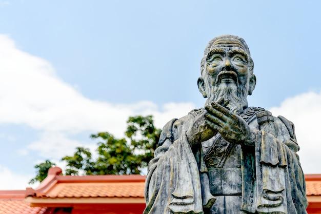 Close-up oud standbeeld van confucius met soft-focus en meer dan licht op de achtergrond