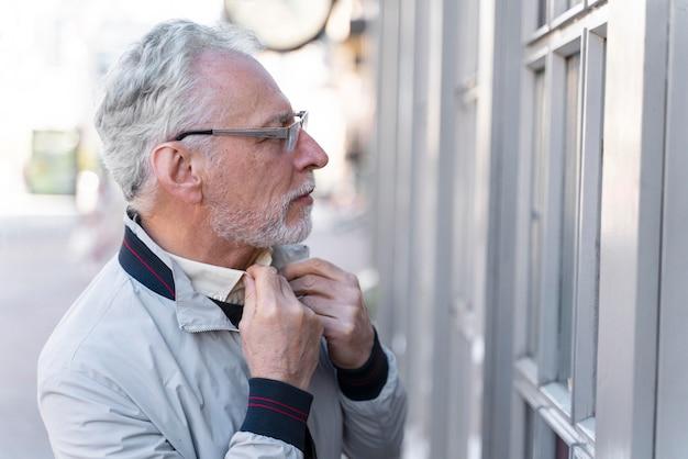 Close-up oude man die zijn shirt schikt