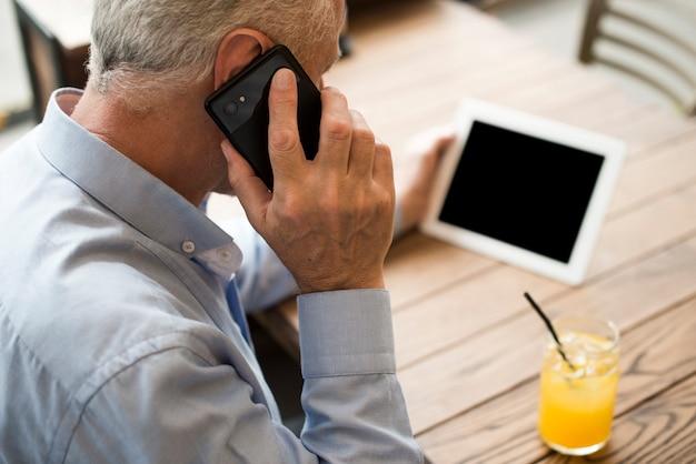 Close-up oude man praten aan de telefoon