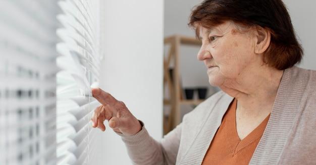 Close-up oude vrouw kijkt uit het raam